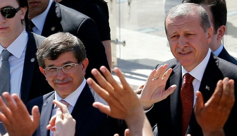 Turkey's Prime Minister Tayyip Erdogan and Foreign Minister Ahmet Davutoglu greet their supporters as they leave Friday prayers in Ankara